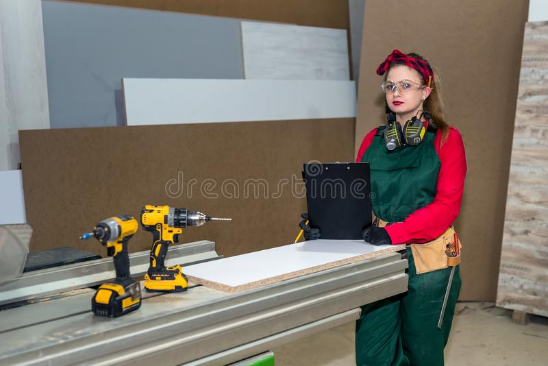 Woman carpenter with drill machine at workplace royalty free stock photography