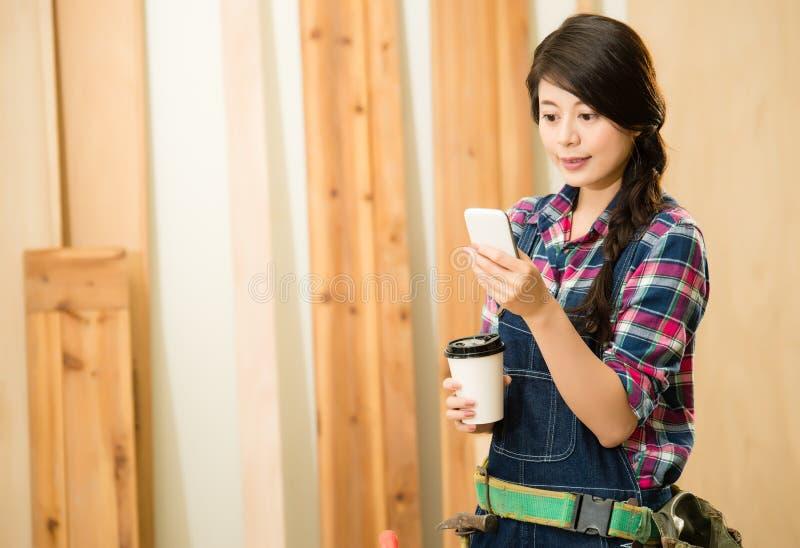 Woman carpenter texting someone stock photo