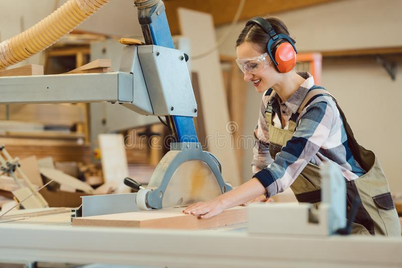 Woman carpenter working with wood at the table saw royalty free stock images