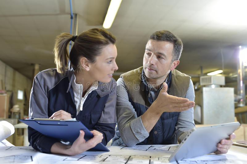 Woman and carpentry instructor using tablet stock image