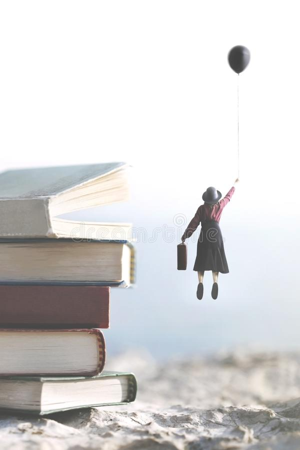 Woman carried by a balloon flies above a mountain of giant books. Woman carried by a balloon flies above a mountain of big books stock image
