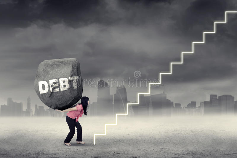 Woman carries heavy rock with Debt word. Young woman carries heavy rock with Debt word on her back and climbing a stairway. Concept of big debt and difficult stock photo