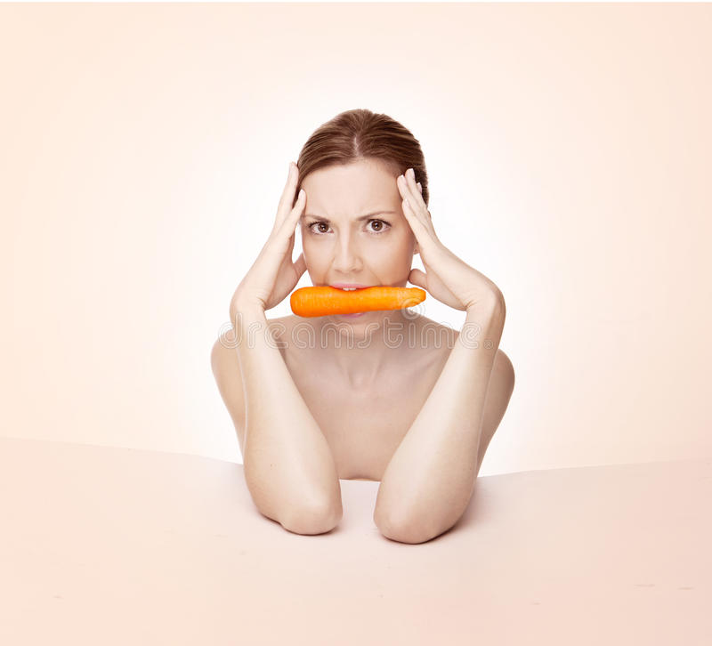 Woman with carrot in mouth royalty free stock images