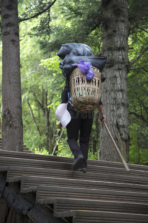 Woman carry heavy goods up mountain stock photography