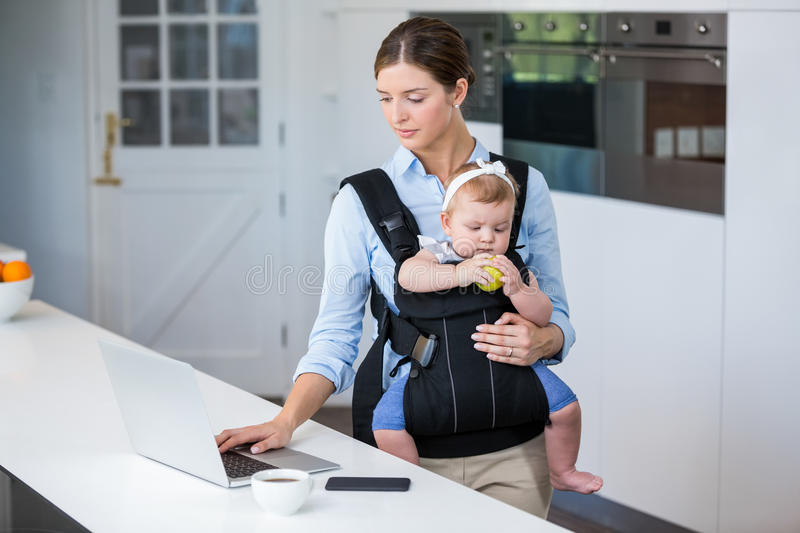Woman carrying baby girl while using laptop at table royalty free stock photos
