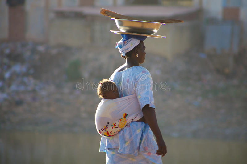 Woman carrying a baby in Mopti stock photo
