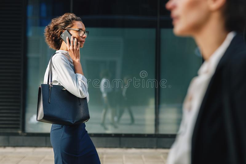 Woman carrying bag walking on city street. To the office and making a call stock photos