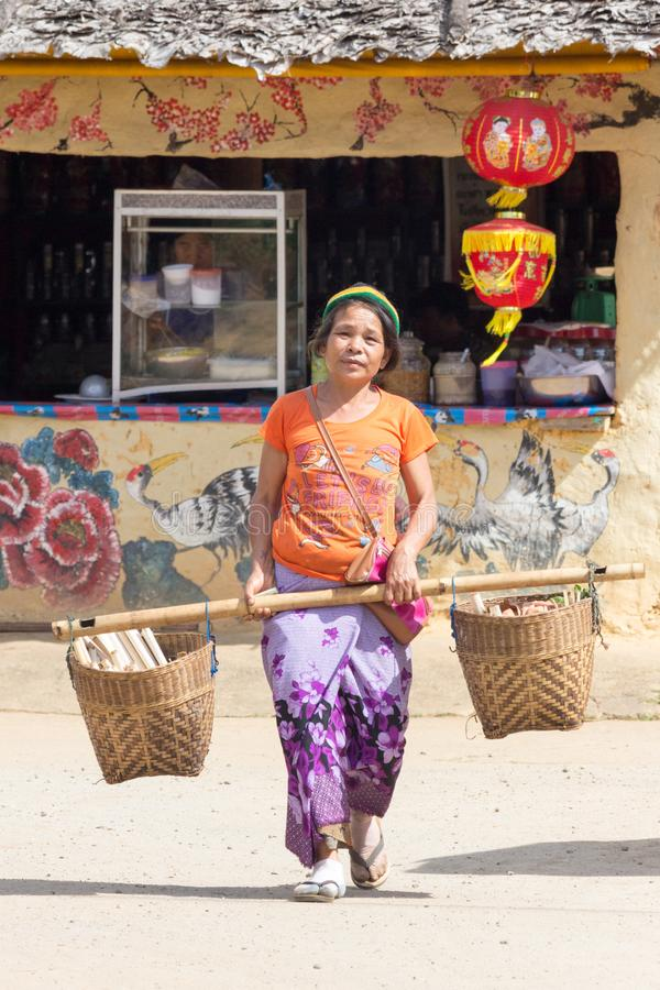 Woman carrying baskets in the Kuomintang CHinese village of Mae Aw or Baan Rak Thai, Mae Hong Son, Thailand. Mae Aw, Thailand - December 9th 2014: Woman carrying royalty free stock images