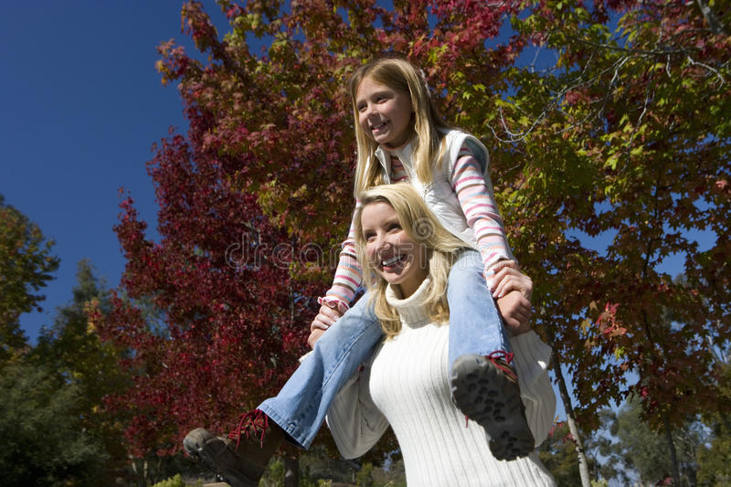Woman carrying daughter on her shoulders stock images