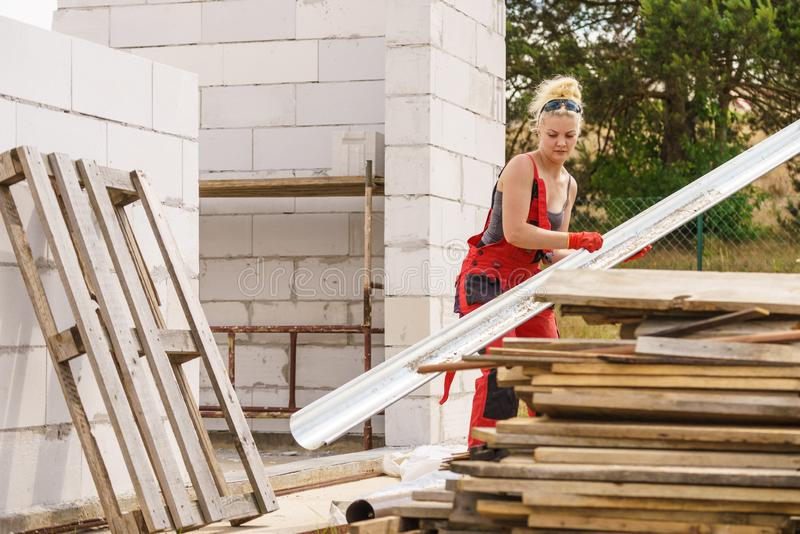 Woman carrying gutter on construction site stock photos