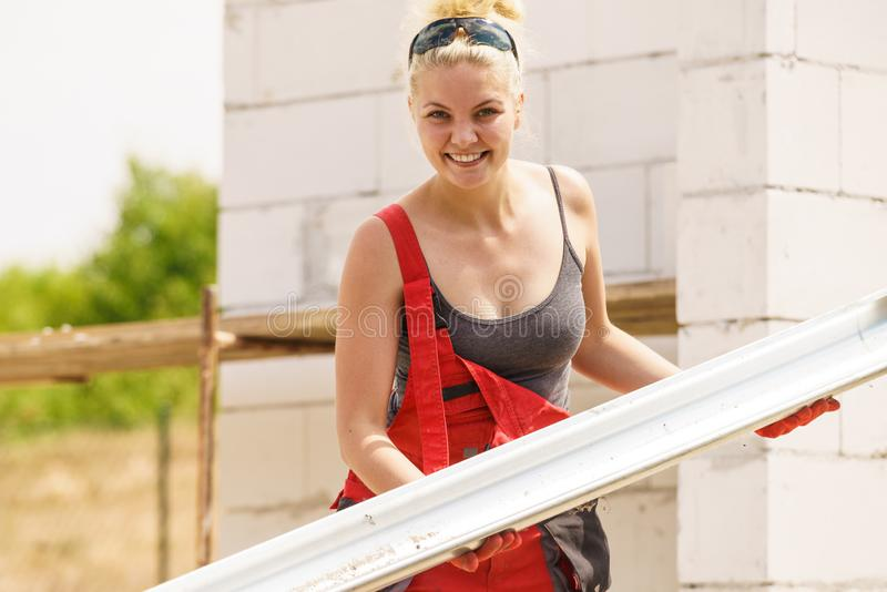 Woman carrying gutter on construction site stock images