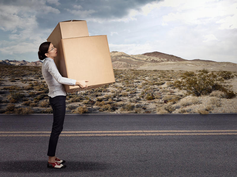 Woman carrying heavy large box package royalty free stock photo