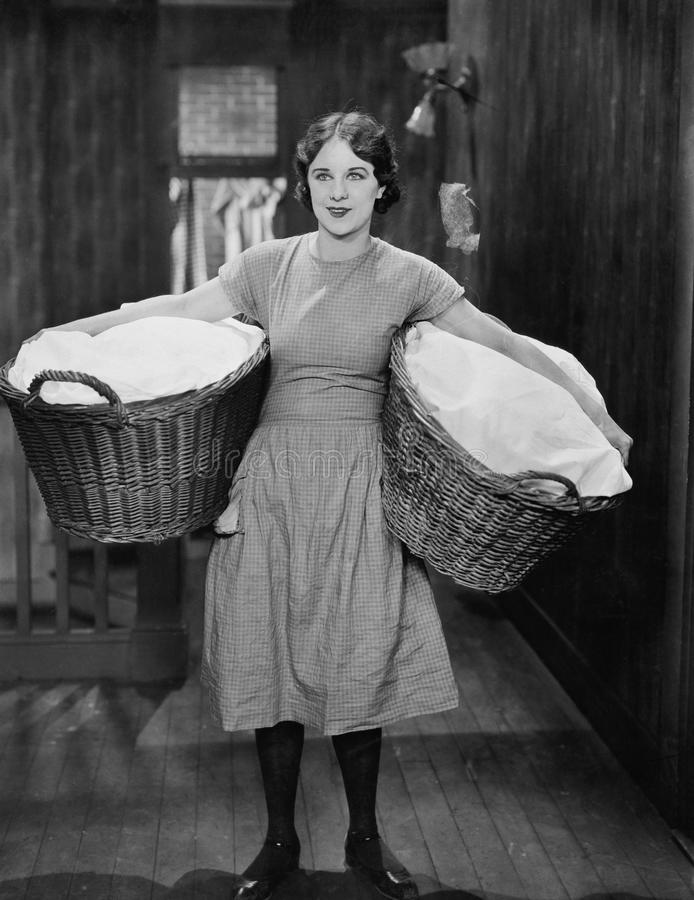 Woman carrying laundry baskets royalty free stock images