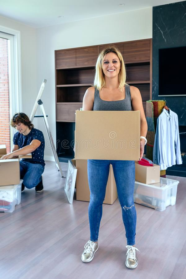 Woman carrying moving box. While her husband unpacks stock images
