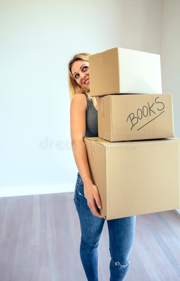 Woman carrying moving boxes stock image