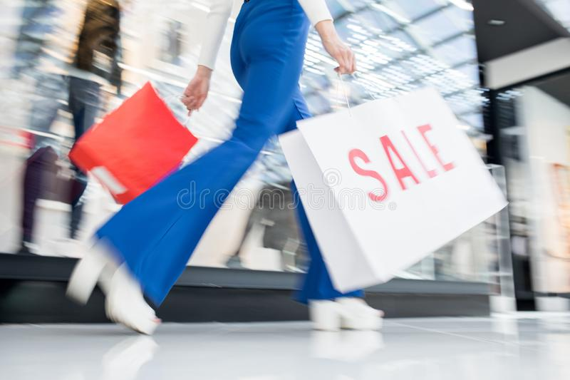 Woman carrying paper bag with Sale inscription stock photos