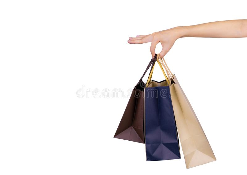 Woman carrying paper shopping bags isolated on white background. Adult woman hand hold three shopping bag with blue and brown royalty free stock images