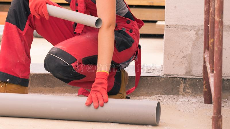 Woman carrying pipes on construction site royalty free stock photos