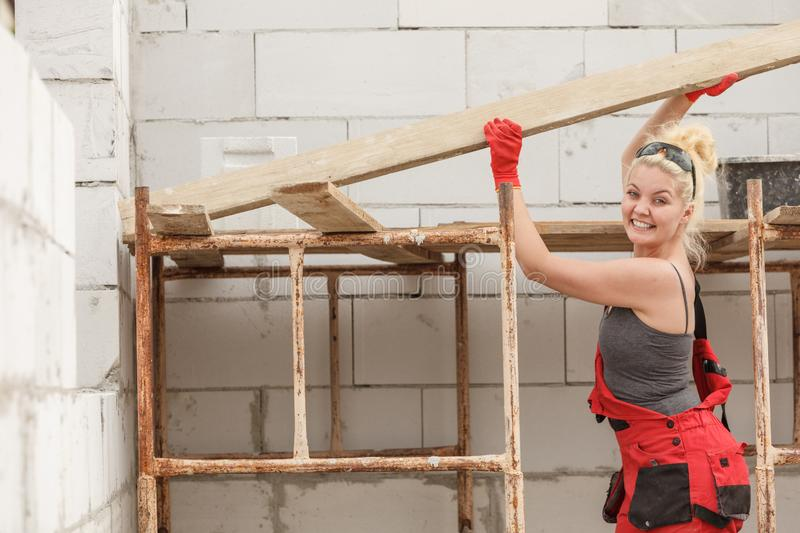 Woman carrying plank boards on construction site stock photo