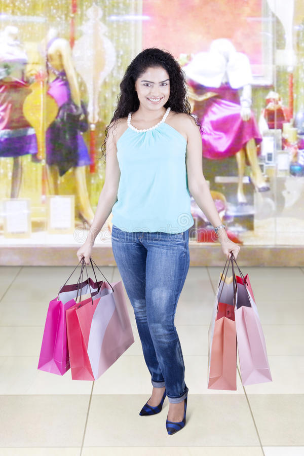 Woman carrying shopping bags in the fashion boutique stock photography
