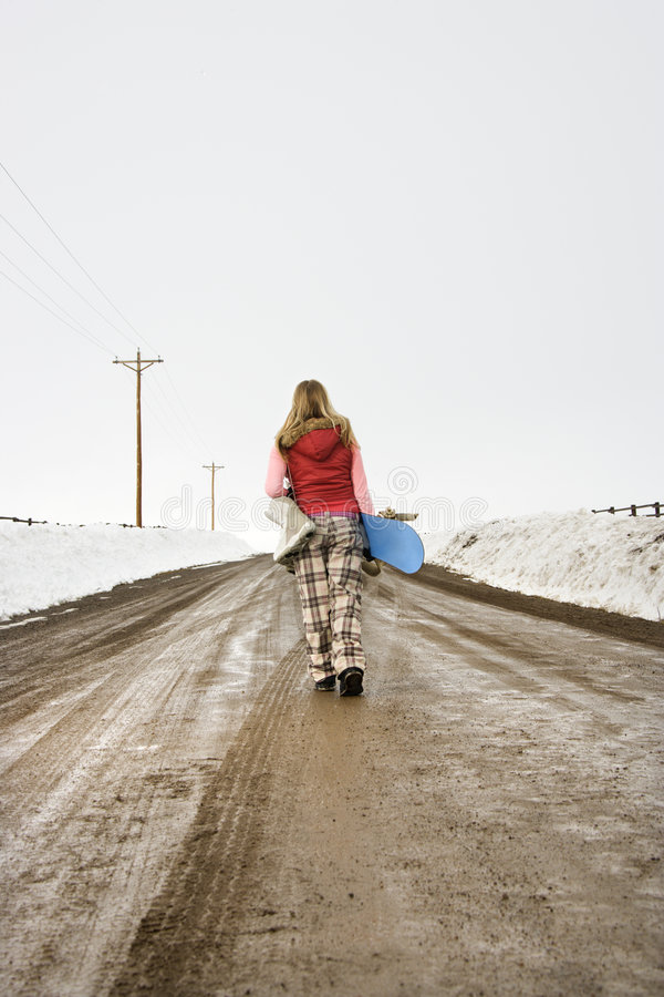 Woman Carrying Snowboard. Royalty Free Stock Images