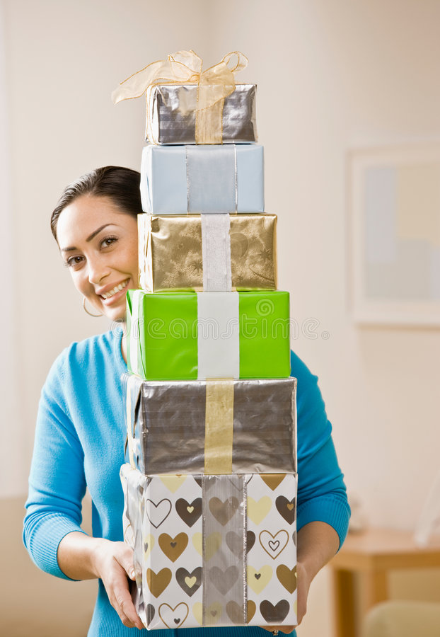 Woman carrying stack of festive birthday gifts. Generous woman carrying stack of festive birthday gifts stock image