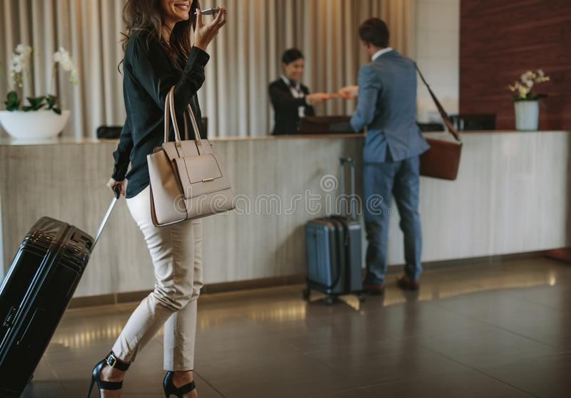 Woman arriving at hotel lobby with suitcase. Woman carrying suitcase and talking on mobile phone in a hotel lobby. Traveler female walking with her luggage in royalty free stock photo