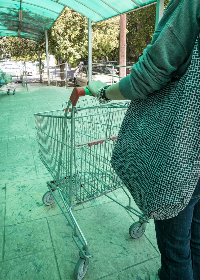 Woman carrying a supermarket trolley. Woman carrying an empty supermarket shopping trolley. Daylight, outdoors closeup stock image