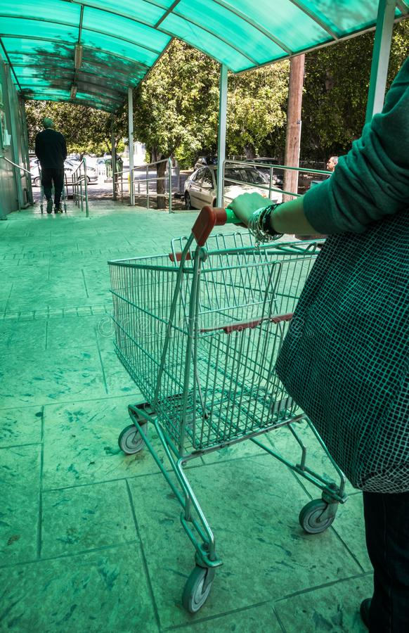 Woman carrying a supermarket trolley. Woman carrying an empty supermarket shopping trolley. Daylight, outdoors closeup royalty free stock images