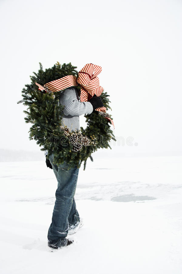 Download Woman Carrying Wreath Through Snow Stock Image - Image of carry, person: 12732655