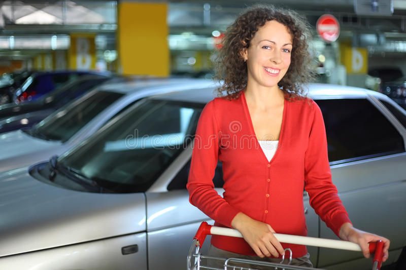 Woman with cart standing in underground car park stock photography