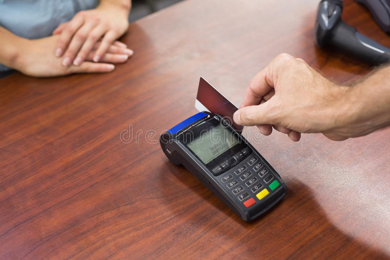 Woman at cash register paying with credit card. In supermarket stock photos