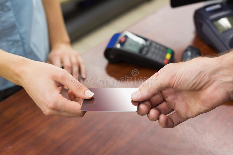Woman at cash register paying with credit card. In supermarket stock image