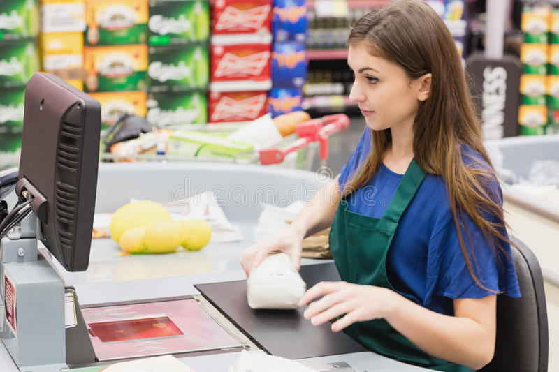 Woman cashier beeping an item. On a grocery royalty free stock photography