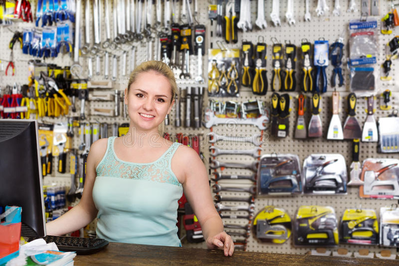 Woman cashier at pay desk. Smiling blond woman cashier standing at pay desk in the household store stock image