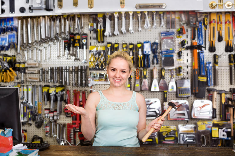 Woman cashier at pay desk. Smiling blond woman cashier standing at pay desk in household store stock images