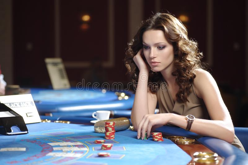 Woman in casino. Young beautiful woman playing blackjack in casino stock images