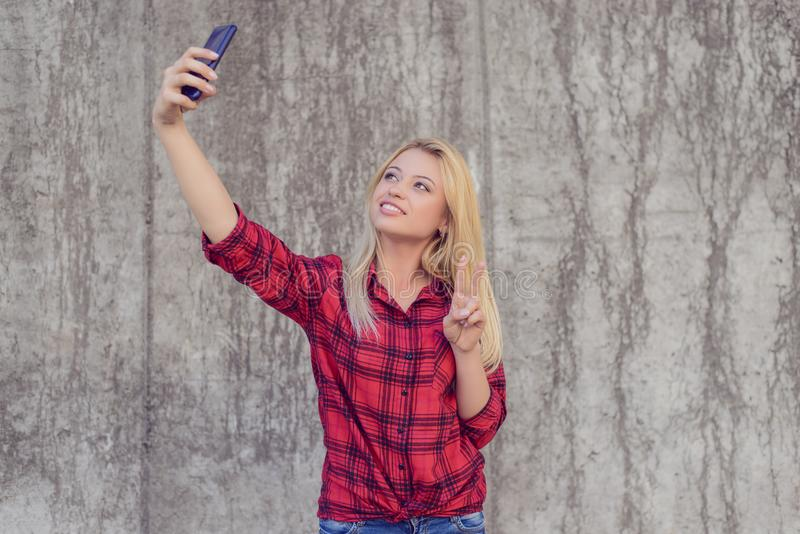 Woman in casual clothes with beaming smile taling selfie on her. Smartphone and showing v-sign royalty free stock image