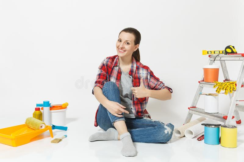 Woman in casual clothes show thumbs up, sit on floor with instruments for renovation apartment room isolated on white stock images