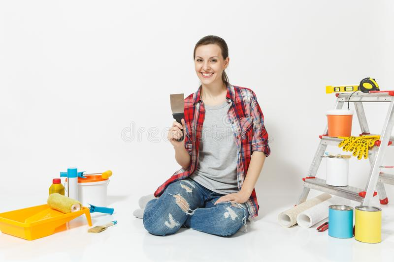 Woman in casual clothes sitting on floor with putty knife, instruments for renovation apartment room isolated on white royalty free stock photo