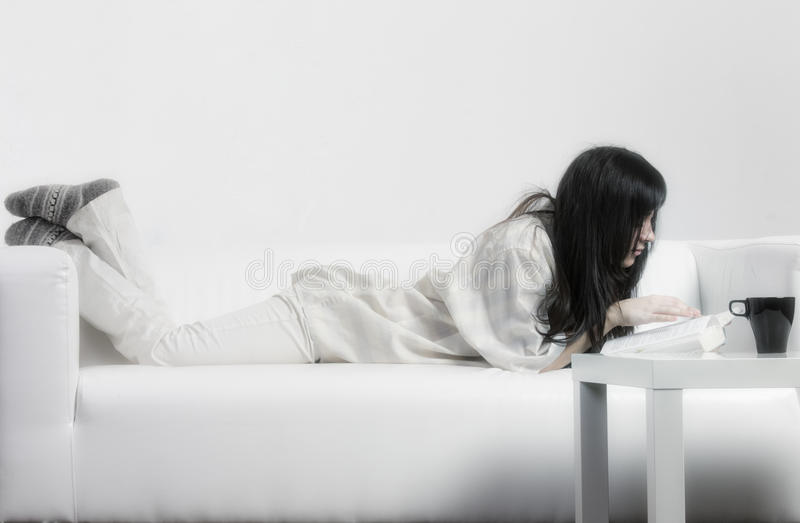 Woman in casual reading on couch royalty free stock photo