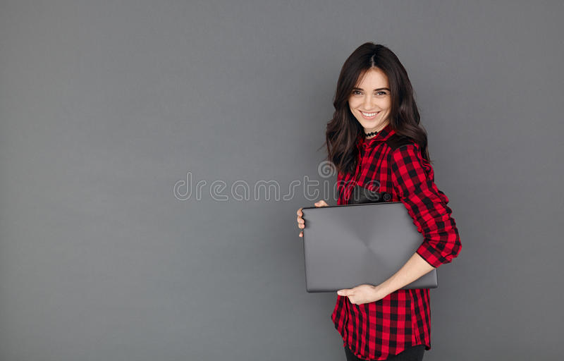 Woman in casual shirt smiling and holding a laptop. Happy young brunette woman in casual shirt smiling and holding a laptop on gray background with copy space royalty free stock image