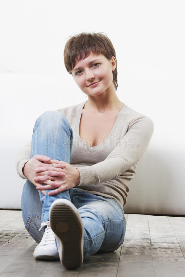 Woman in casual sitting on floor stock image