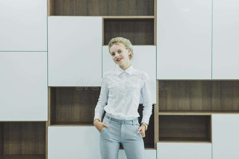 Woman in casual wear in office. Attractive young smiling woman in casual wear in office royalty free stock photo