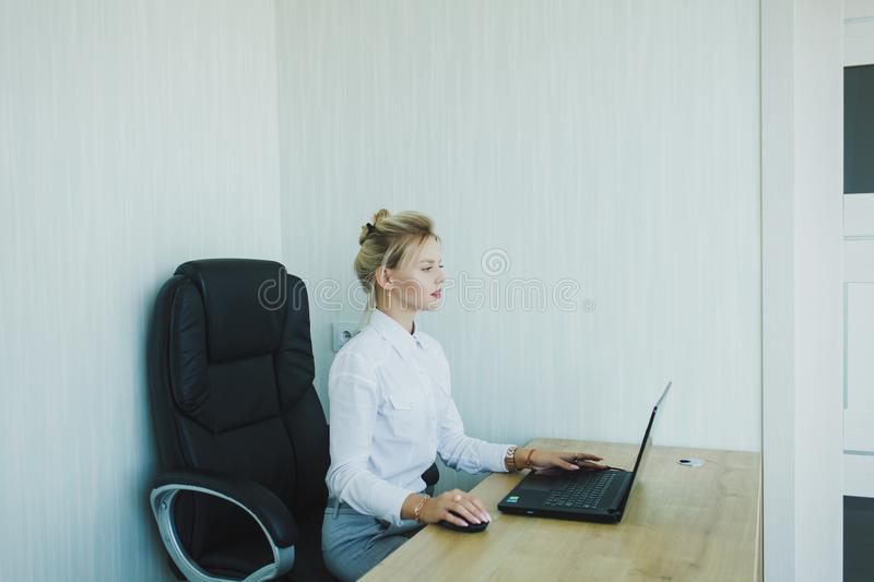 Woman in casual wear working on laptop royalty free stock photography