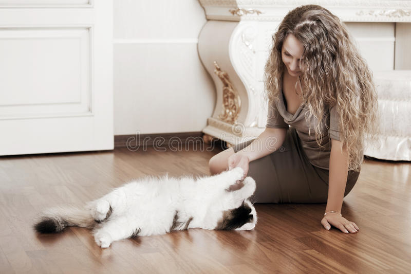 Fashion woman playing with a cat at apartment. Beautiful fashion woman playing with a cat on the floor at apartment royalty free stock photo