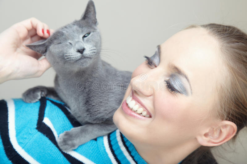 Woman and cat. Smiling woman holding and pampering cat indoors stock images