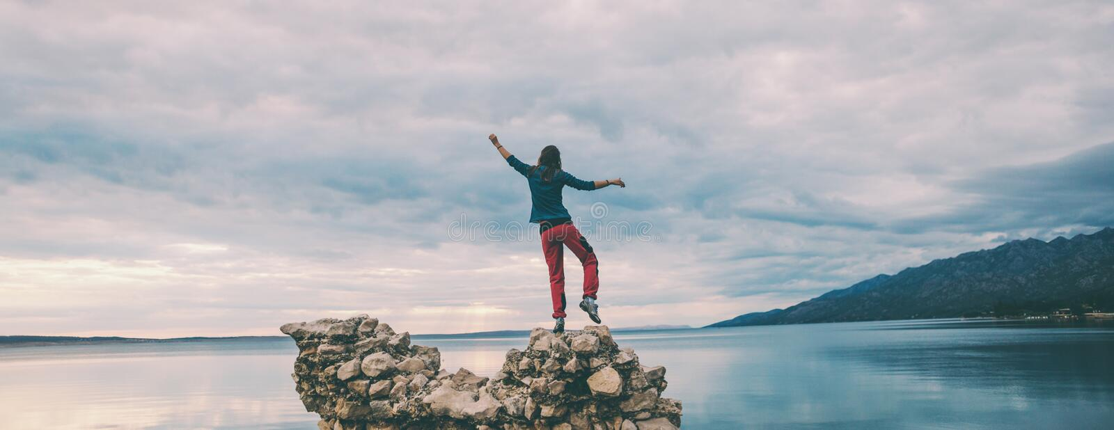 Woman catches balance on the stone stock photo