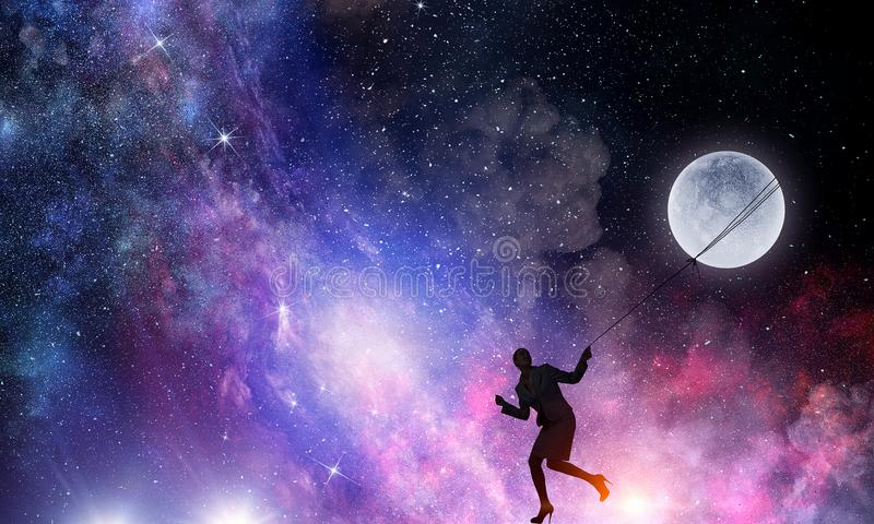 Woman catching moon . Mixed media royalty free stock image