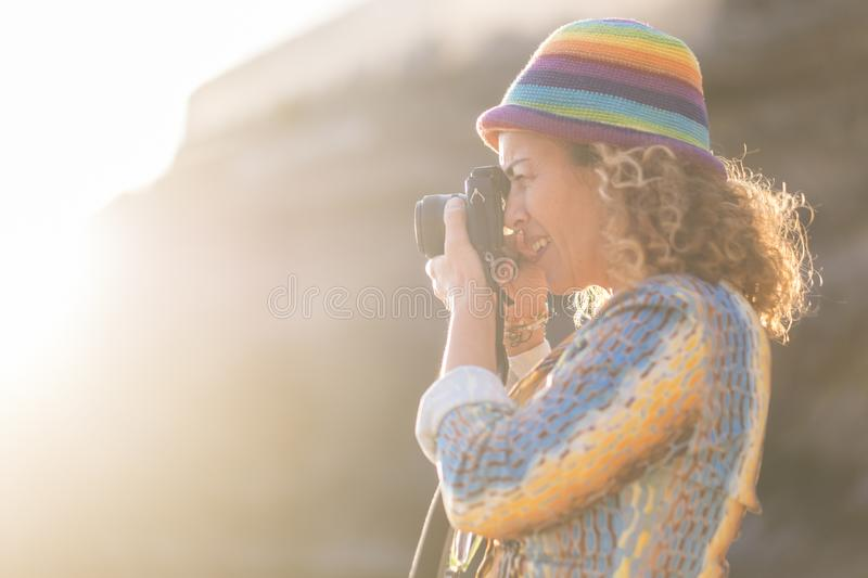 Woman caucasian photographer with nice coloured hat taking pictures with old little camera. sunlight and sun flare in the. Background. bright summer concept royalty free stock photo
